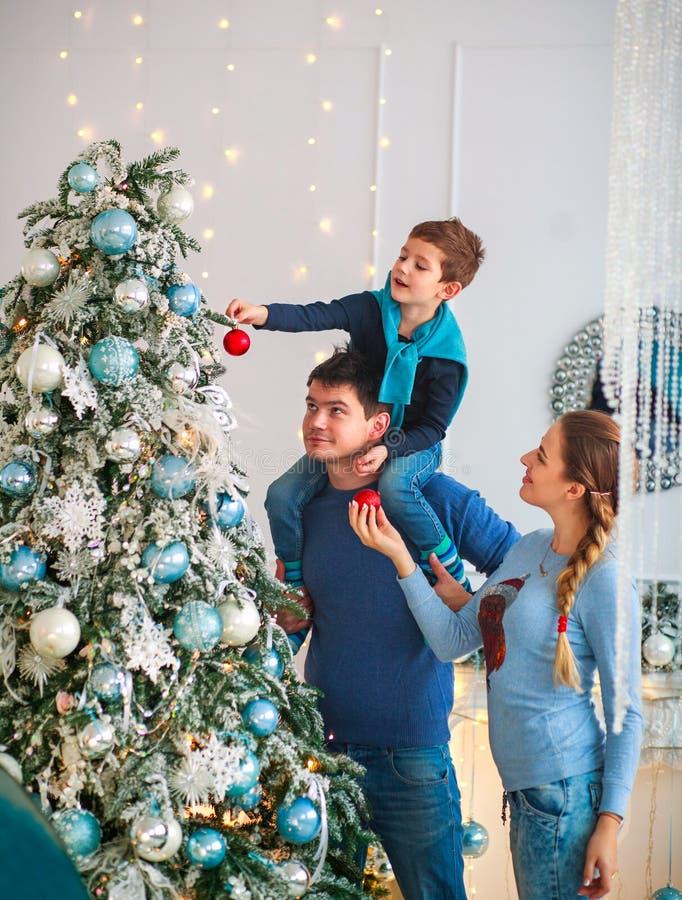Den lyckliga vänliga familjen som dekorerar julgranen, har gyckel fotografering för bildbyråer