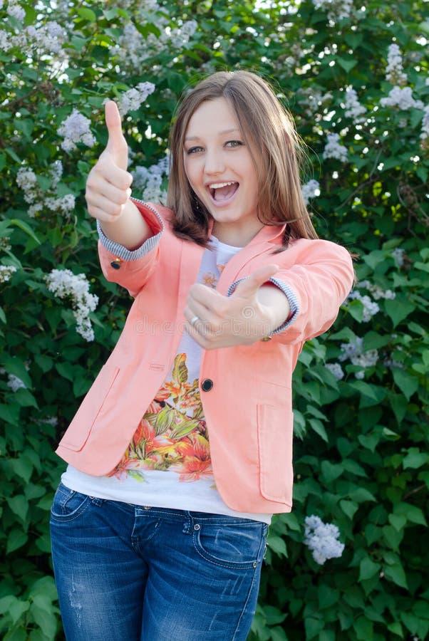 Den lyckliga visningen för tonårs- flicka tummar upp på bakgrunden för sommar utomhus royaltyfria bilder