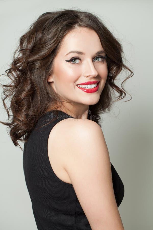 Den lyckligt kvinnan med makeup och lockigt guppar frisyren Le modellst?enden arkivbild