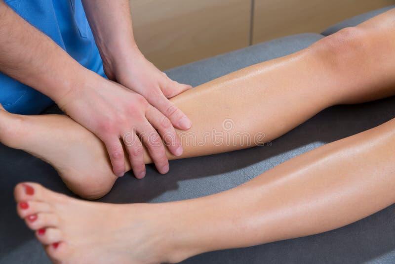 Den Lymphatic dräneringmassageterapeuten räcker på kvinna lägger benen på ryggen arkivbild