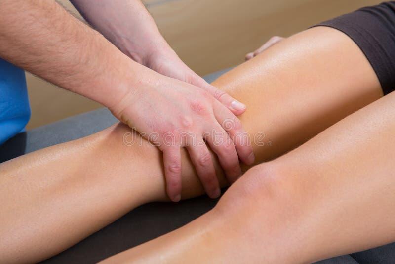 Den Lymphatic dräneringmassageterapeuten räcker på kvinna lägger benen på ryggen royaltyfri foto
