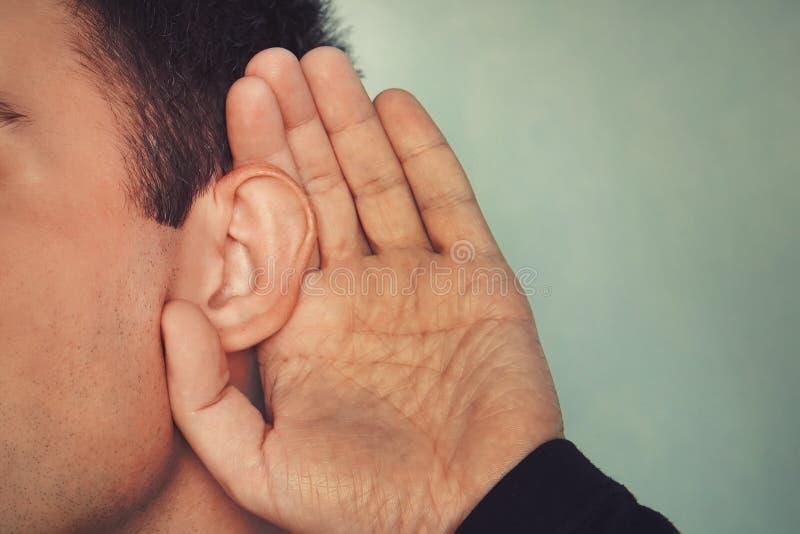 Den lyssnande mannen rymmer hans hand nära hans öra begrepp av dövhet eller tjuvlyssnandet hård hearing royaltyfri fotografi