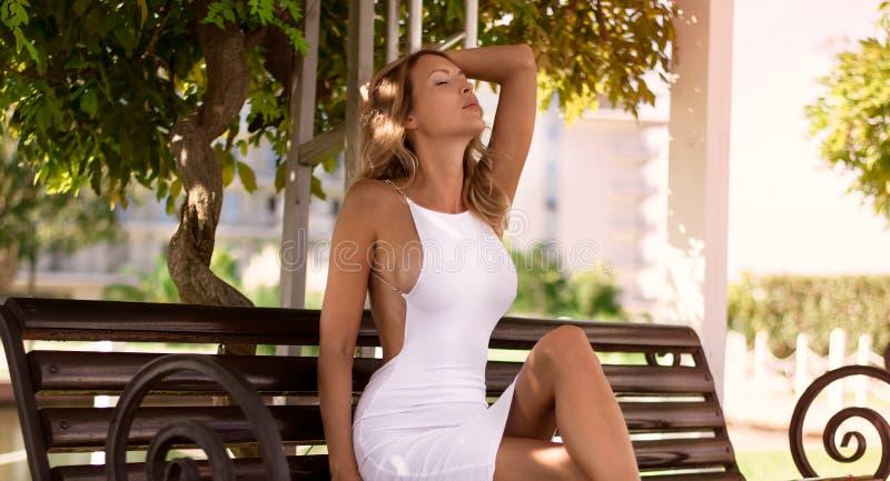 Den lyxiga härliga slanka blondinen i en sexig vit klänning och hög-heeled sandaler sitter på en bänk i parkerar fotografering för bildbyråer