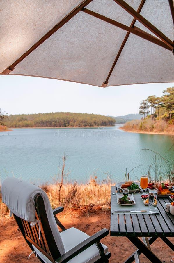 Den lyxiga lakesidepicknicktabellen ställde in med mat och drinken arkivfoton