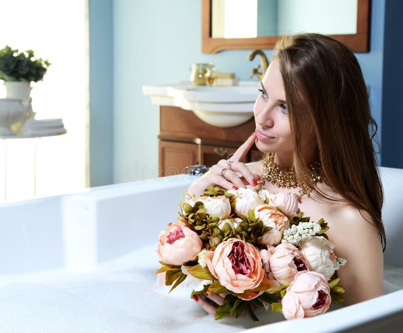 Den lyxiga modekvinnan i hotellbrunnsorten som ligger i bad, badar med buketten av blommor royaltyfria foton