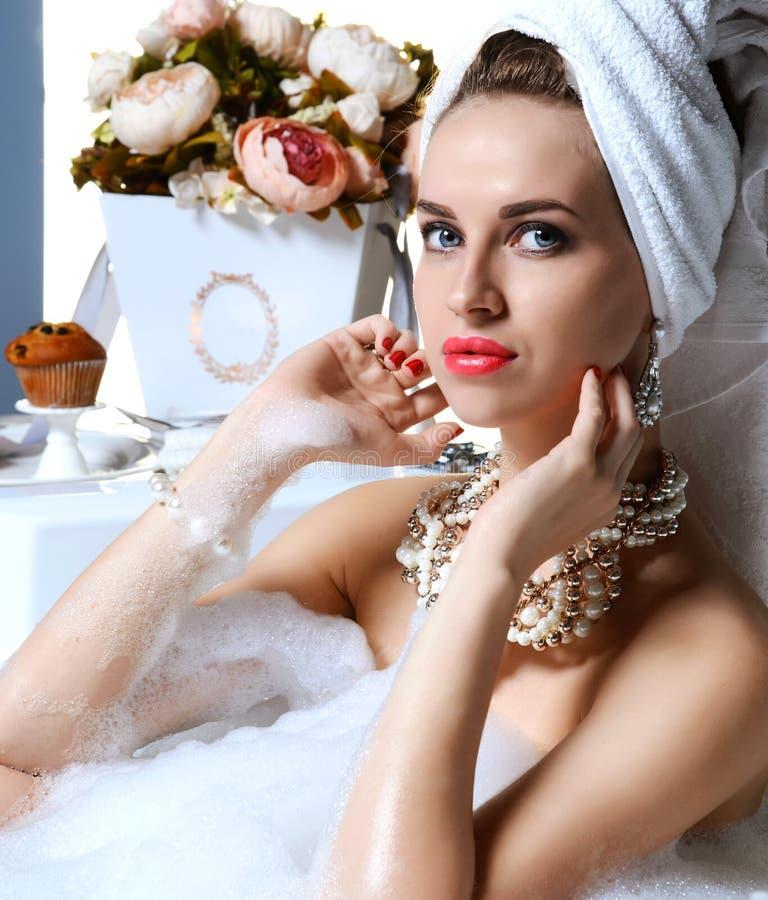 Den lyxiga modekvinnan i hotellbrunnsorten som ligger i bad, badar med buketten av blommor arkivfoto