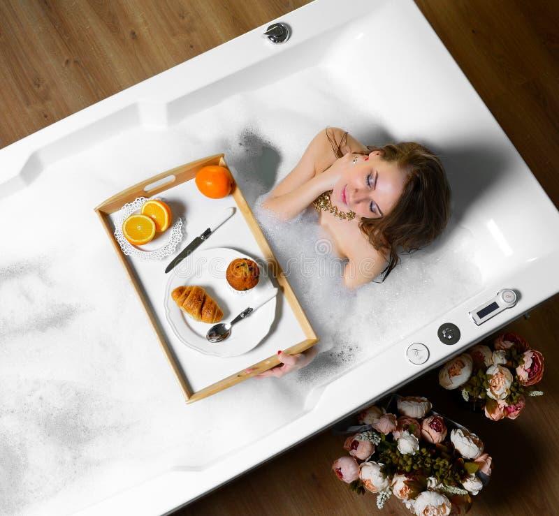 Den lyxiga modekvinnan i morgontagandefrukosten i hotellbrunnsorten som ligger i bad, badar arkivbild