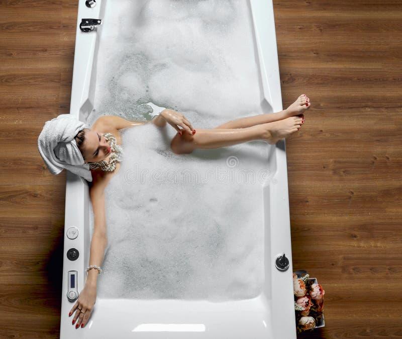Den lyxiga modekvinnan med den mjuka stora handduken i morgonhotellbrunnsorten som ligger i bad, badar royaltyfri foto