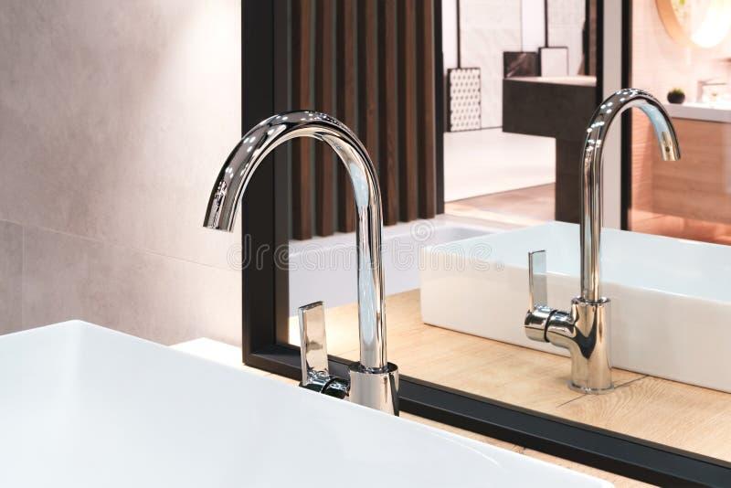 Den lyxiga stora vattenkranblandaren på den vita rektangulära vasken i inre av det härliga beigea gråa badrummet och reflekte fotografering för bildbyråer