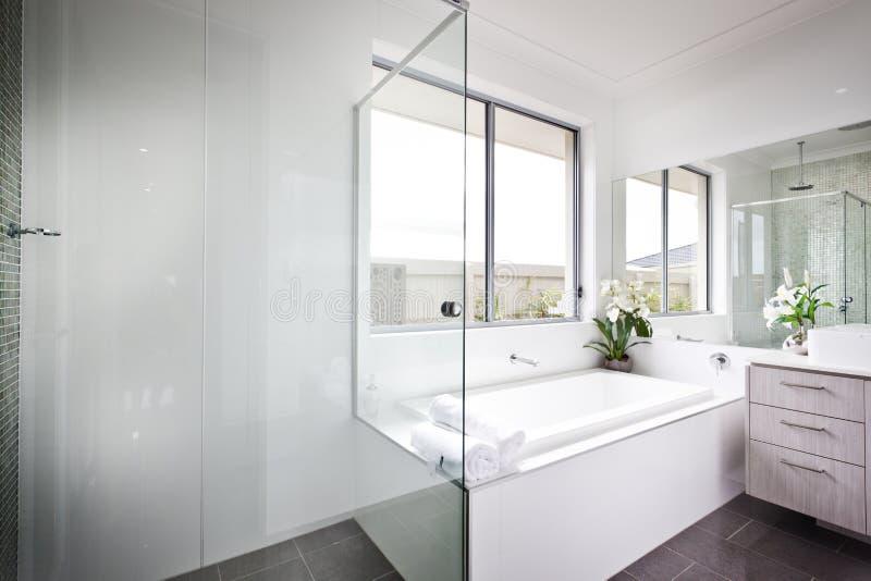 Den lyxiga toaletten med vita v?ggar och badet badar royaltyfria bilder