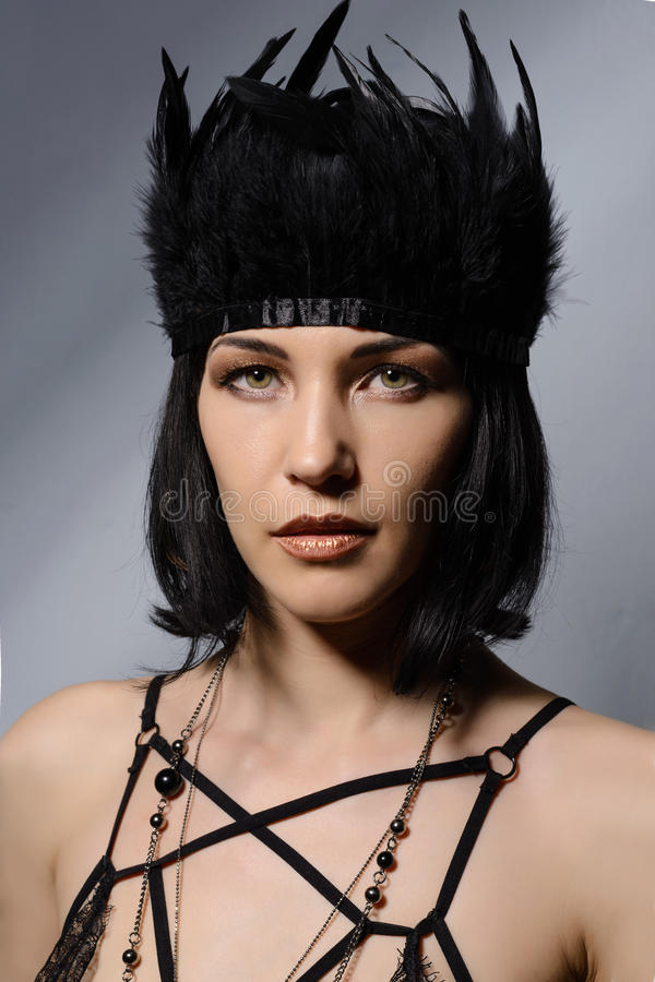 Den lyxiga unga kvinnan med svart befjädrar i hennes hår arkivbilder