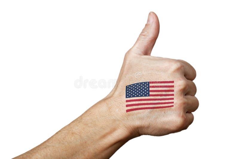 Den mänskliga handen med tummen gör en gest upp och USA flaggan arkivfoto