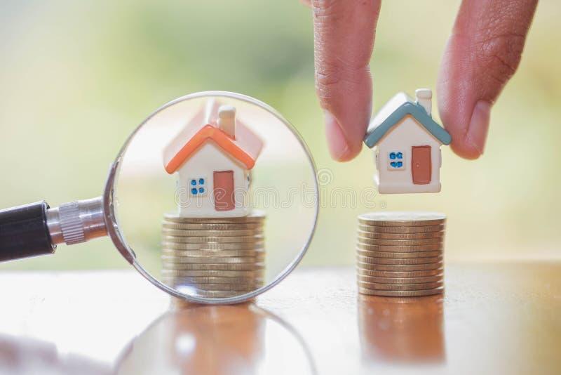 Den mänskliga handen rymmer huset på myntet som planerar besparingpengar av mynt för att köpa ett hem- begrepp, intecknar och fas royaltyfri fotografi