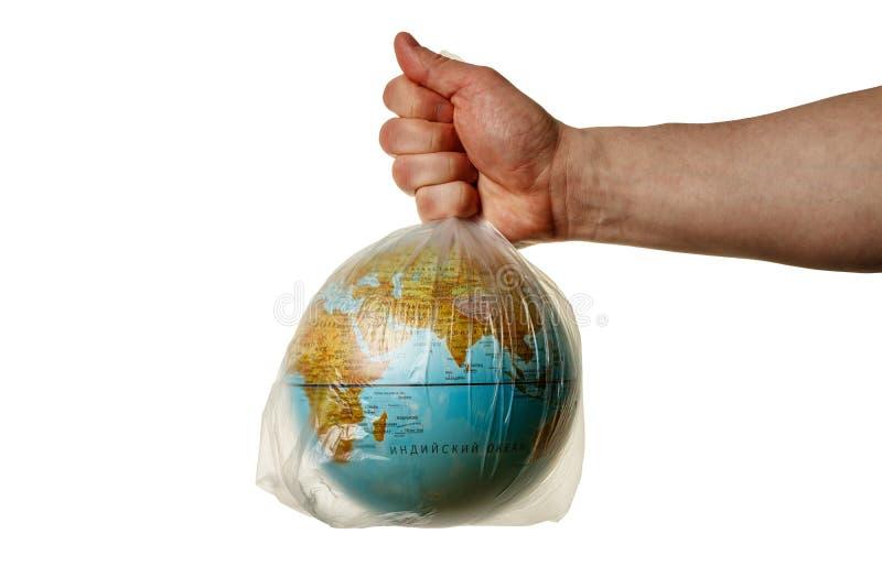 Den mänskliga handen rymmer planetjorden i en plastpåse royaltyfri fotografi