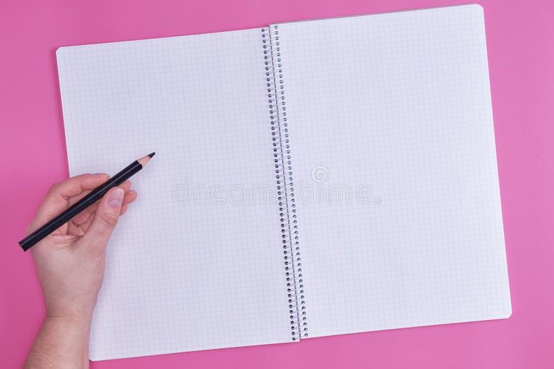 Den mänskliga handen rymmer den svarta träblyertspennan över den tomma öppna anteckningsboken royaltyfria foton