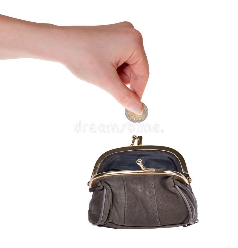 Den mänskliga handen satte euromyntet i handväska på vit royaltyfri foto