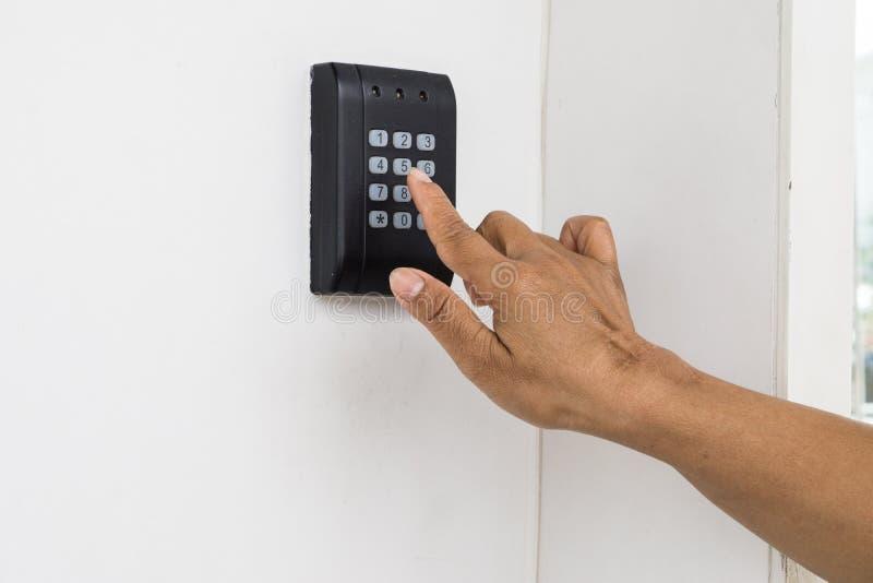 Den mänskliga handen trycker på på knappen som skriver in säkerhetssystemkod arkivfoton