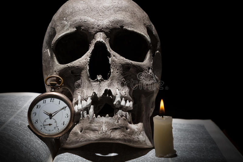 Den mänskliga skallen på den gamla öppna boken med bränningstearinljuset och tappning tar tid på på svart bakgrund under stråle a arkivfoto