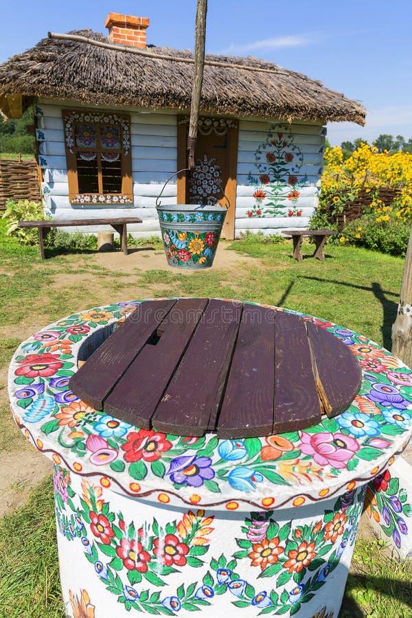 Den målade gamla trästugan, brunnen och hinken som dekoreras med en målad hand, blommar, Zalipie, Polen royaltyfria foton