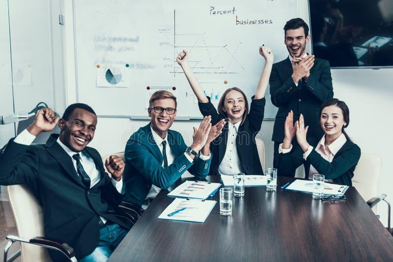 Den mång- folkgruppen av lyckat affärsfolk jublar på framgång i konferenskorridor royaltyfri bild
