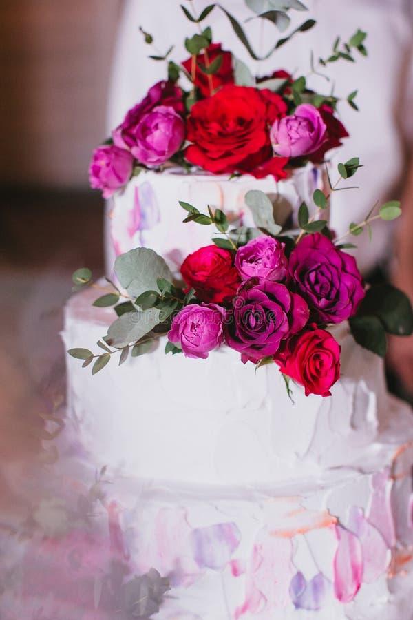 Den mång- tiered härliga bröllopstårtan med vitkräm dekorerade med rosa och röda rosor och eukalyptuns royaltyfri foto