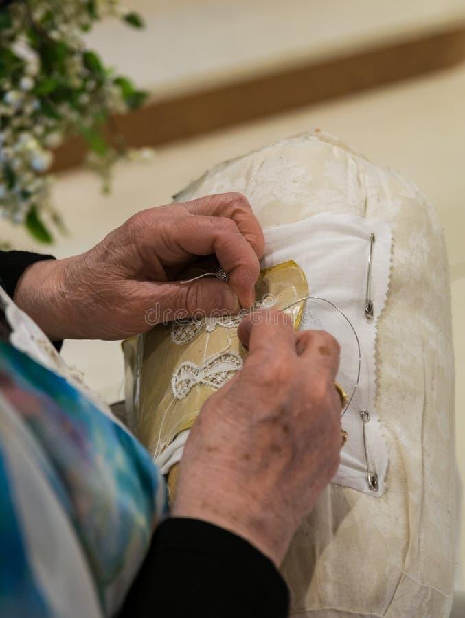 Den månghundraåriga hantverkvisaren snör åt av Burano royaltyfri foto