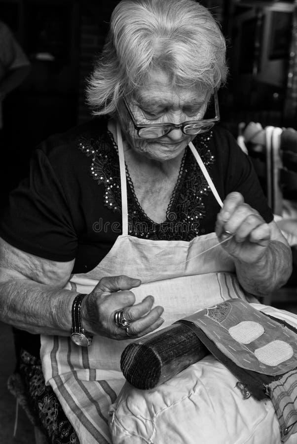 Den månghundraåriga hantverkvisaren snör åt av Burano arkivfoton