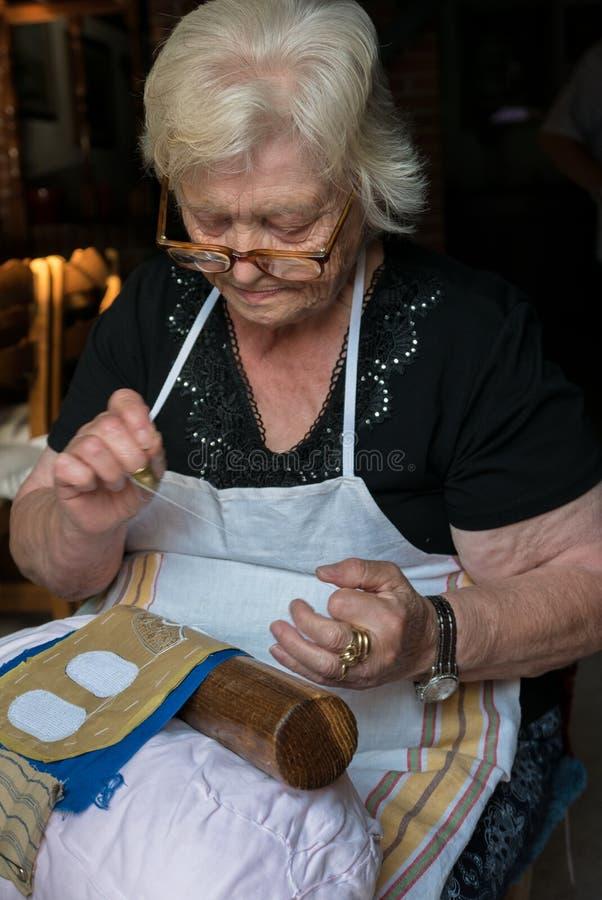 Den månghundraåriga hantverkvisaren snör åt av Burano royaltyfri fotografi