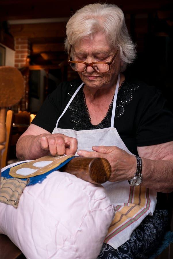 Den månghundraåriga hantverkvisaren snör åt av Burano arkivfoto