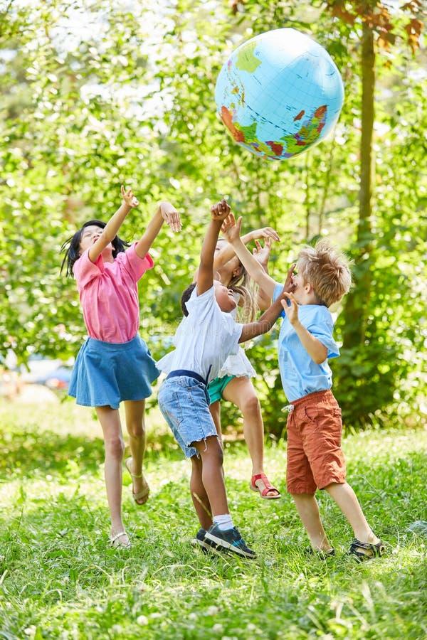 Den mångkulturella gruppen av ungar spelar med världsjordklotet royaltyfri foto