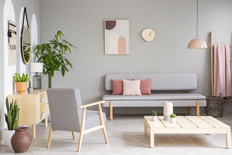 Den mönstrade träfåtöljen bredvid tabellen i grå färger sänker inrewi royaltyfria foton
