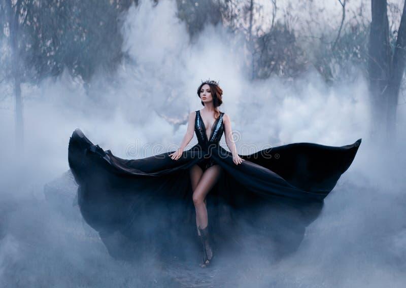 Den mörka drottningen, med kala långa ben, går dimma En lyxig svart klänning blossar i olika riktningar, som vingarna arkivfoto