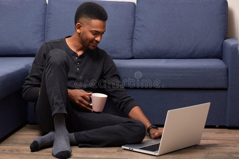 Den mörka flådde unga mannen som hemma arbetar med hans bärbar dator, rymmer koppen med den varma drycken som sitter nära soffan  royaltyfria foton