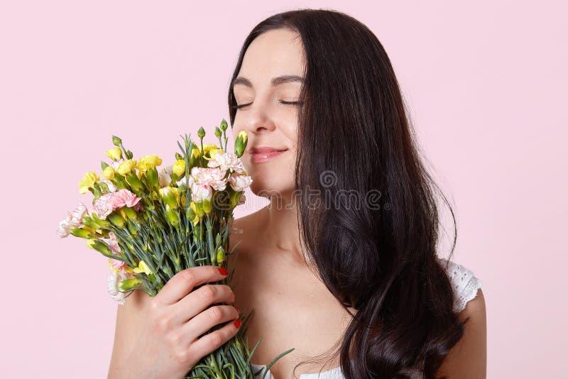 Den mörka haired unga damen, iklädd vit klänning, har stilfull röd manikyr och att stå med stängda ögon som luktar härliga blommo arkivfoto