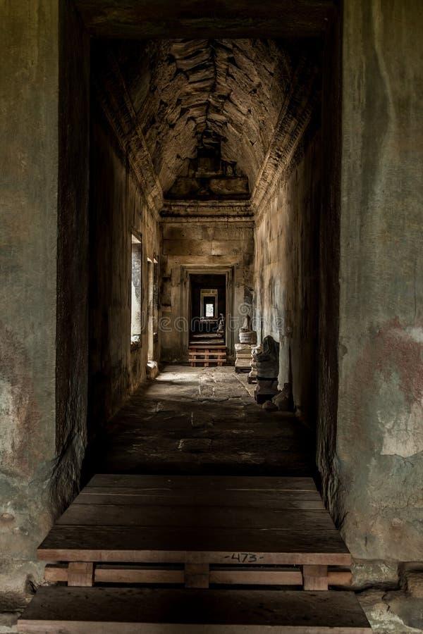 Den mörka korridoren inom den Angkor Wat templet som är arkeologisk parkerar, Siem Reap, Cambodja royaltyfria bilder