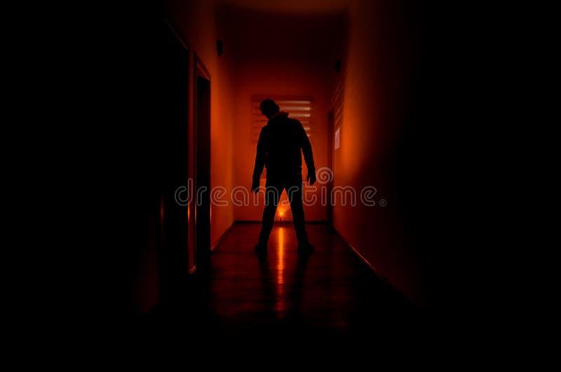 Den mörka korridoren med kabineda dörrar och ljus med konturn av den spöklika fasan man anseende med olikt poserar arkivbild