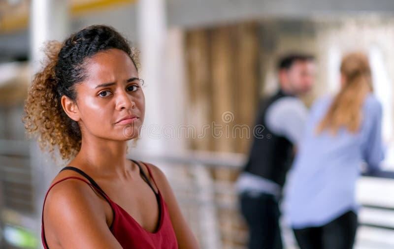Den mörka solbrända kvinnan för det blandade loppet för hud agerar som upprivet eller olyckligt, när hon grundar hennes samtal fö royaltyfri fotografi