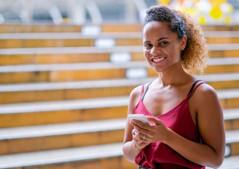 Den mörka solbrända kvinnan för det blandade loppet för hud att rymma hennes mobiltelefon och att se framåtriktat och också att s royaltyfri foto