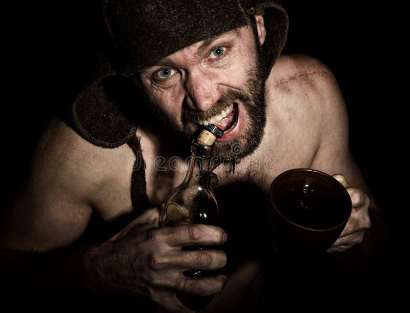 Den mörka ståenden av den läskiga onda illavarslande skäggiga mannen med flin, öppnar han en flaska av konjak hans tänder konstig royaltyfria foton