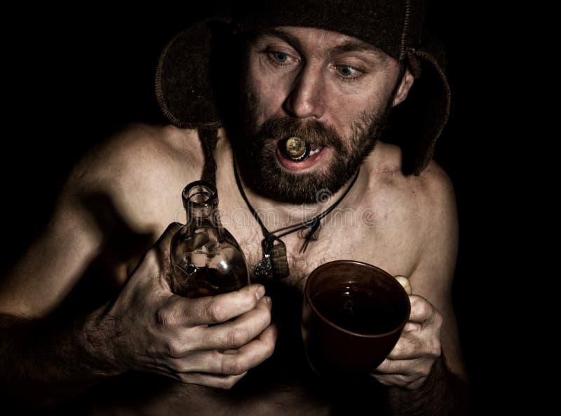 Den mörka ståenden av den läskiga onda illavarslande skäggiga mannen med flin, öppnar han en flaska av konjak hans tänder konstig royaltyfri fotografi