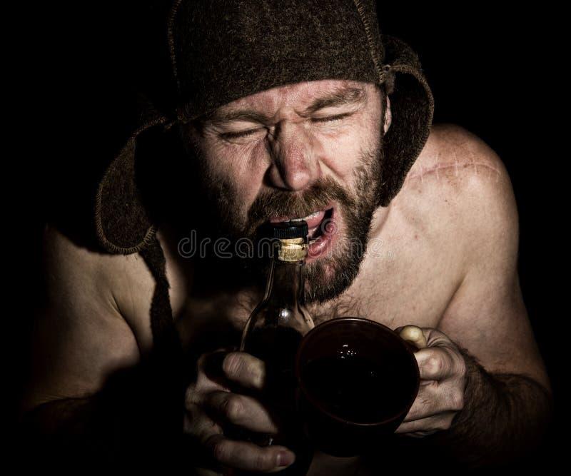 Den mörka ståenden av den läskiga onda illavarslande skäggiga mannen med flin, öppnar han en flaska av konjak hans tänder konstig arkivbilder