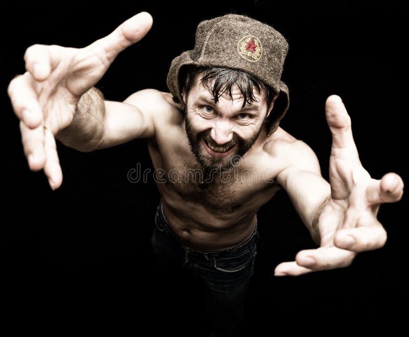 Den mörka ståenden av den läskiga onda illavarslande skäggiga mannen med flin, gör den olika handens tecken och uttrycker olika s royaltyfri bild
