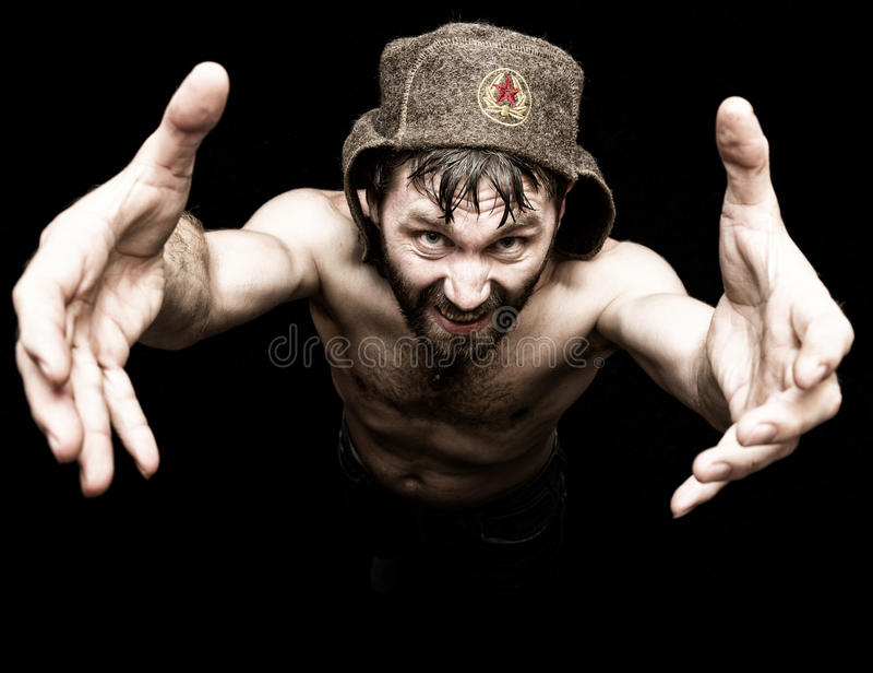 Den mörka ståenden av den läskiga onda illavarslande skäggiga mannen med flin, gör den olika handens tecken och uttrycker olika s arkivfoton
