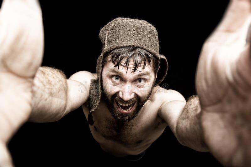 Den mörka ståenden av den läskiga onda illavarslande skäggiga mannen med flin, gör den olika handens tecken och uttrycker olika s arkivfoto