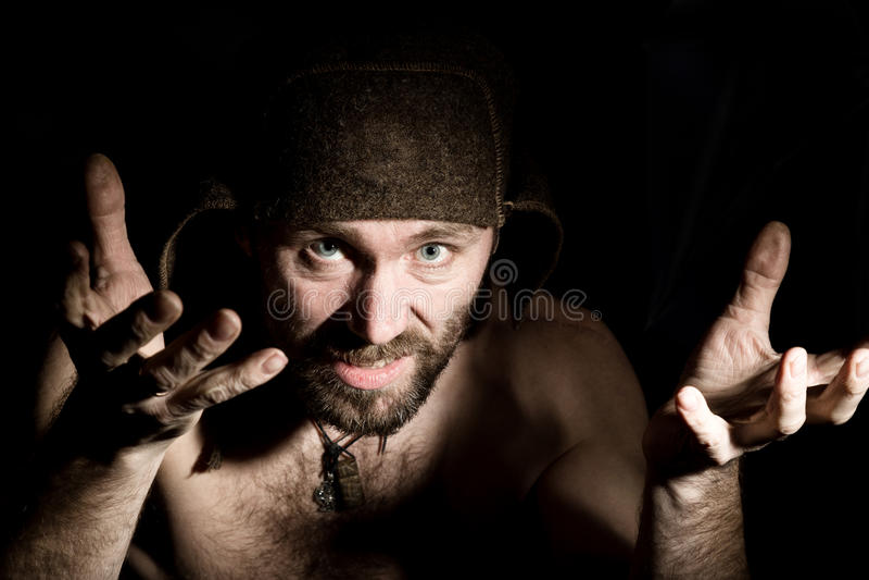 Den mörka ståenden av den läskiga onda illavarslande skäggiga mannen med flin, gör olik hand& x27; s undertecknar och uttrycker o royaltyfri bild