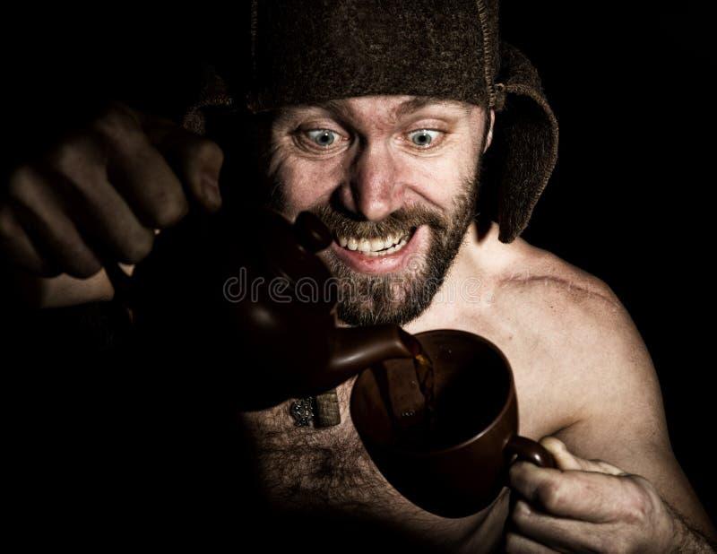 Den mörka ståenden av den läskiga onda illavarslande skäggiga mannen med flin, häller han konjak i en kopp kaffe konstig rysk man arkivfoto