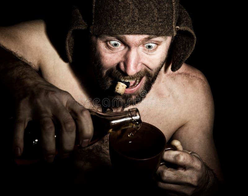 Den mörka ståenden av den läskiga onda illavarslande skäggiga mannen med flin, häller han konjak i en kopp kaffe konstig rysk man royaltyfri bild