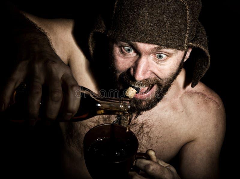 Den mörka ståenden av den läskiga onda illavarslande skäggiga mannen med flin, häller han konjak i en kopp kaffe konstig rysk man royaltyfria foton