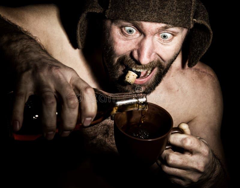 Den mörka ståenden av den läskiga onda illavarslande skäggiga mannen med flin, häller han konjak i en kopp kaffe konstig rysk man arkivfoton