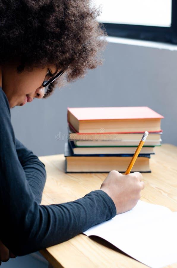 Den mörkhyade flickan som sitter på tabellen, undervisar kurser fotografering för bildbyråer